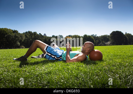 Young man lying on grass with head on basketball - Stock Photo