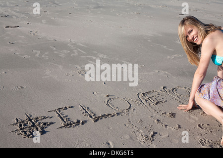 Young woman writing love message in sand, Breezy Point, Queens, New York, USA - Stock Photo