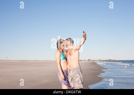 Couple taking self portrait on beach, Breezy Point, Queens, New York, USA - Stock Photo
