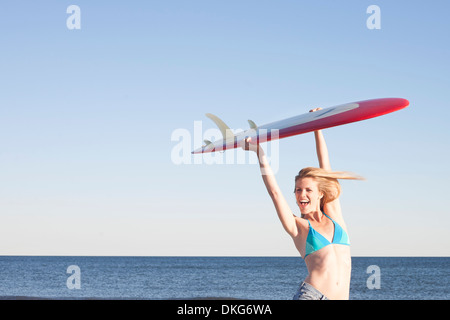 Young woman holding surfboard up, Breezy Point, Queens, New York, USA - Stock Photo