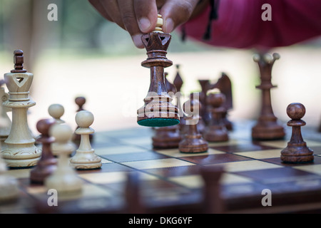 Hand moving chess piece on board, close up - Stock Photo
