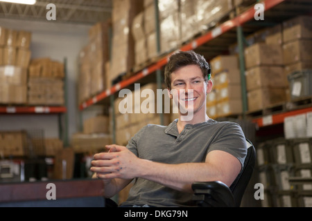 Worker sitting in warehouse - Stock Photo