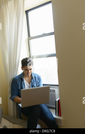 Young man sitting on window sill using laptop - Stock Photo