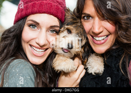 Friends holding pet dog for photograph - Stock Photo