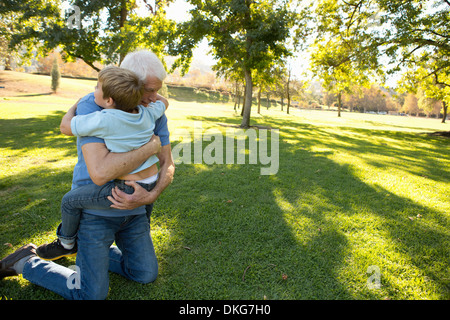 Grandfather kneeling on grass hugging grandson - Stock Photo
