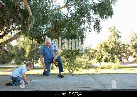 Grandfather and grandson drawing hopscotch - Stock Photo