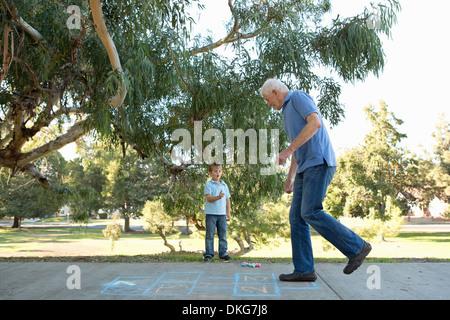 Grandfather on hopscotch, boy watching - Stock Photo