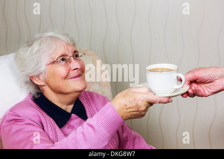 Frail sweet happy old elderly senior woman looking and smiling at a carer handing her a cup of tea during daily - Stock Photo