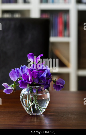 Vase with purple vech on a wooden table - Stock Photo