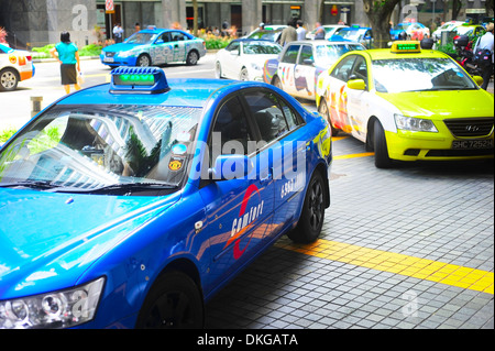 Taxi cabs on the road in Singapore. - Stock Photo