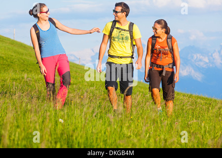 Young people mountain hiking on alpine meadow in the Osterhorn Group, Salzburg State, Austria - Stock Photo