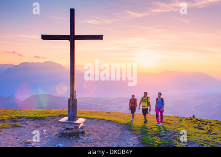 Young people at sunset at summit cross in the Osterhorn Group, Salzburg State, Austria - Stock Photo