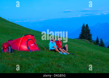 Young couple with tent in mountain meadow in the Osterhorn Group, Salzburg State, Austria - Stock Photo
