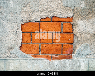 Old damaged rendering revealing inner wall of brick courses - France. - Stock Photo