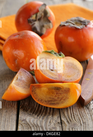 persimmon fruit whole and sliced on a wooden table - Stock Photo