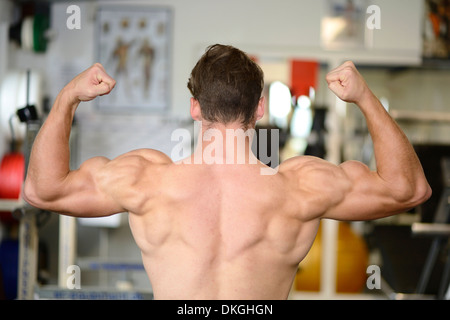 Young man posing in fitness center, rear view - Stock Photo