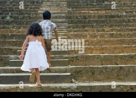 Two siblings, a 5-year-old MR Indian boy and a 4-year-old MR Guatemalan girl, run up historic, stone steps at the - Stock Photo