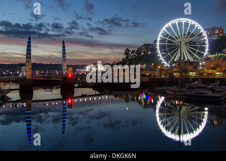 Torquay Harbour Twilight Big Wheel is the dominant feature alongside  the inner harbour footbridge - Stock Photo