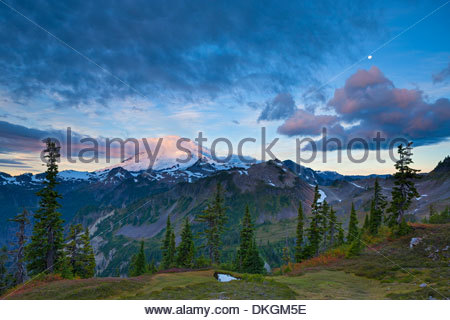 The nearly full moon is visible between layers of storm clouds over Mount Baker, a volcano in the North Cascades, - Stock Photo