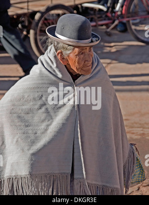Elderly indigenous lady wearing grey shawl and bowler hat in Peruvian Andean village of Moho, South America - Stock Photo