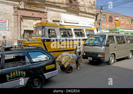 Man with barrow / hand cart loaded with goods stuck in traffic jam among buses and taxis in congested street in - Stock Photo