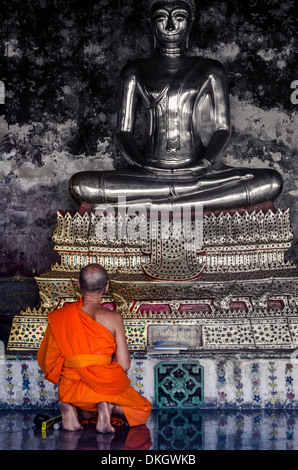 A monk prays in front of a golden Buddha, Wat Suthat, Bangkok, Thailand, Southeast Asia, Asia - Stock Photo