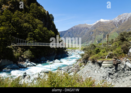 Hikers pause on a suspension bridge in New Zealand to take photographs - Stock Photo