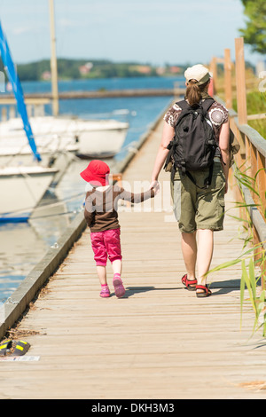 Mother and child looking at sailboats, walking on jetty on sunny summer day. Sweden. - Stock Photo