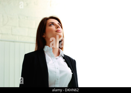 Young businesswoman looking up at copyspace in office - Stock Photo