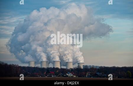 The cooling towers of the brown coal power station of the Vattenfall AG emit columns of smoke behind family homes - Stock Photo