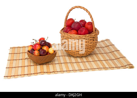 Plums in a wicker basket and cherries in a wooden bowl on a napkin - Stock Photo