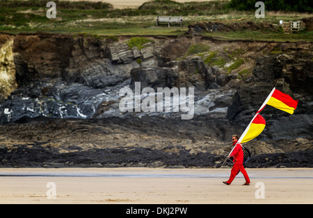 Lifeguard carries waring flags to the waters edge in Cornwall - Stock Photo