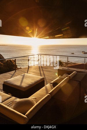 View of sunset over ocean from luxury balcony - Stock Photo