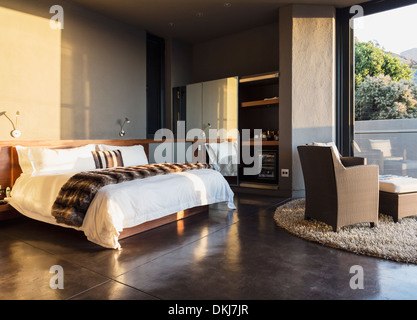 Armchair and bed in modern bedroom - Stock Photo