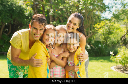 Family relaxing together in backyard - Stock Photo