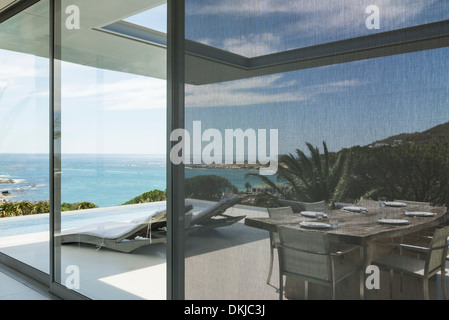 View of ocean beyond patio and swimming pool - Stock Photo