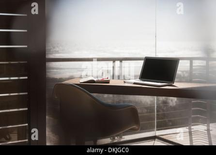 Laptop on desk in modern home office overlooking ocean - Stock Photo