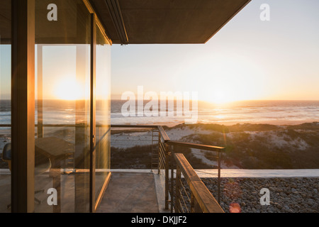 View of sunset over ocean from balcony of modern house - Stock Photo