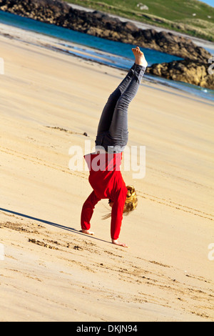 Twelve year old girl performing a handstand  on a sandy beach wearing a red fleece and black jeans with bare feet - Stock Photo