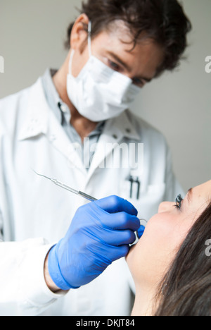 Male dentist wearing blue gloves examining smiling female dental patient - Stock Photo