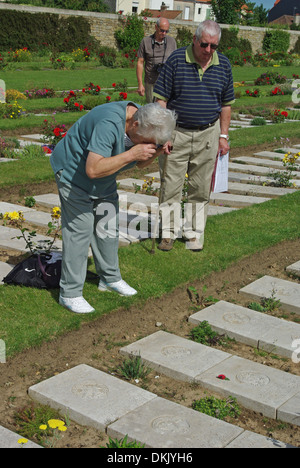 Senior lady taking a photo of a relative's grave in the WW1 cemetery of Boulogne East - Stock Photo