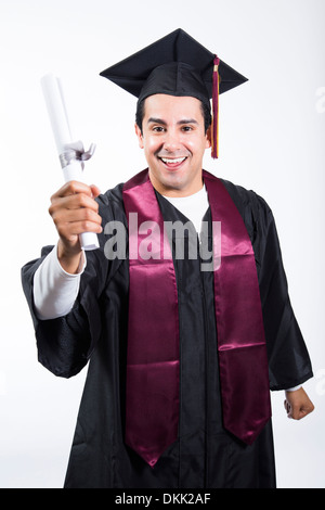 Smiling male graduate holding up diploma - Stock Photo