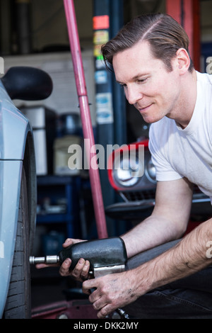 Male mechanic working on car - Stock Photo