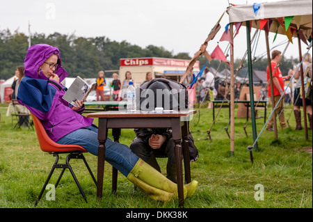 A couple sat at a table outdoors at a music festival. The young man has his head on the table. The woman is reading. - Stock Photo