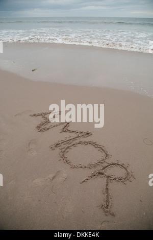 'Amor' written in wet sand - Stock Photo