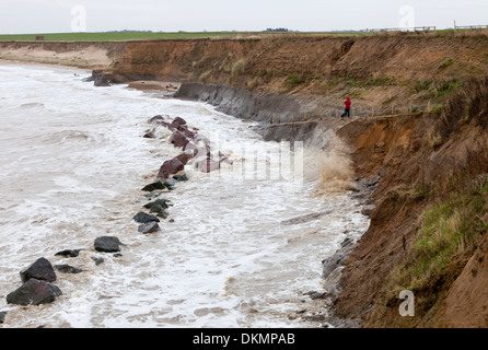 High Tide at Happisburgh in Norfolk England, with a photographer taking pictures from the beach access ramp - Stock Photo