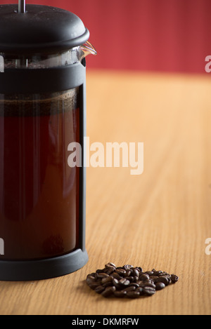 Close up of a cafetiere brewing coffee and some coffee beans on a wooden kitchen table