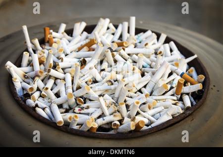 large ashtray full of many cigarette butts - Stock Photo