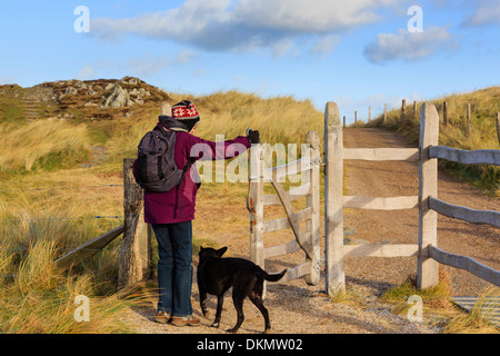Woman walker walking a dog opening kissing gate on main path on Ynys Llanddwyn Island. Newborough Isle of Anglesey - Stock Photo