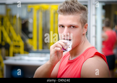 Handsome young man in gym eating cereal bar, looking at camera. - Stock Photo